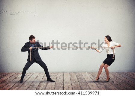 Businessman and businesswoman tug of war contest of strength conflict concept - stock photo
