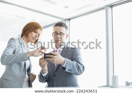 Businessman and businesswoman using cell people in office - stock photo