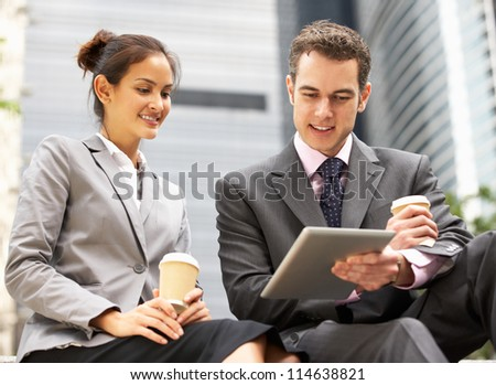 Businessman And Businesswoman Using Digital Tablet Outside Office - stock photo