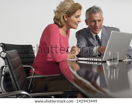 Businessman and businesswoman using laptop in conference room - stock photo
