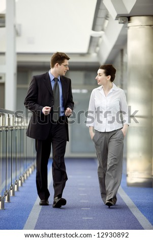 Businessman and businesswoman walking and talking on modern office building corridor. - stock photo