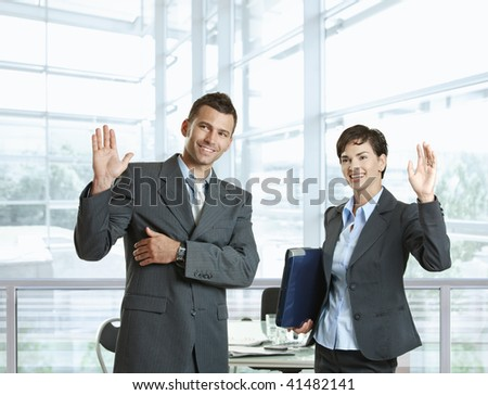Businessman and businesswoman waving hands, greeting somebody before meeting. - stock photo