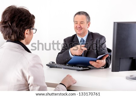 Businessman and businesswoman with documents in the office - stock photo