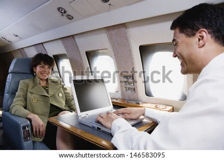 Businessman and businesswoman with laptop on private airplane