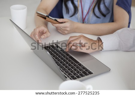 Businessman and businesswoman working with laptops and smart phones at the office - stock photo