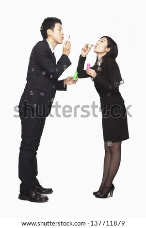 Businessman and businesswomen blowing soap bubbles at each other