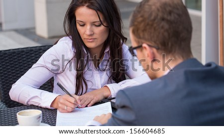 Businessman and businesswomen having a meeting in cafe. She is signing a contract. - stock photo