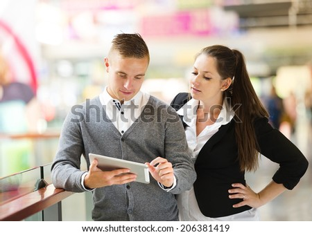 Businessman and businesswomen having a meeting in shopping mall. Woman is pregnant. - stock photo