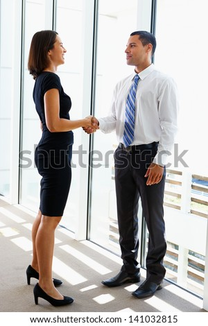 Businessman And Businesswomen Shaking Hands In Office - stock photo