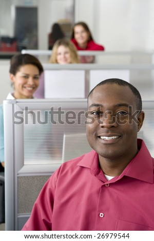 Businessman and co-workers sitting in cubicles - stock photo
