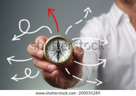 Businessman and compass showing direction concept for guidance, strategy and business orientation - stock photo