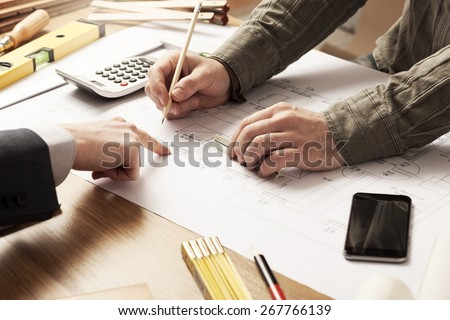 Businessman and construction engineer working together, the customer is pointing on the project on the desk - stock photo