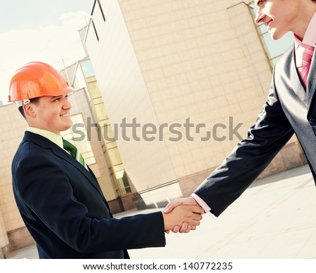 Businessman and engineer  handshaking near building - stock photo
