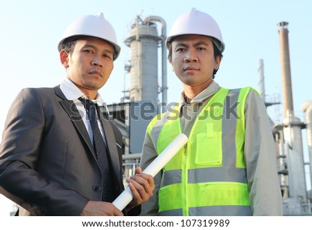 businessman and engineer standing in front of an large oil refinery