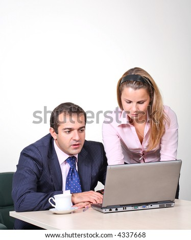 Businessman and female assistant working on laptop