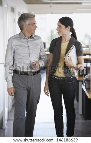 Businessman and female colleague talking in office