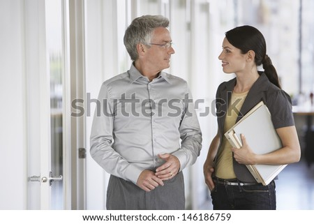 Businessman and female colleague talking in office - stock photo