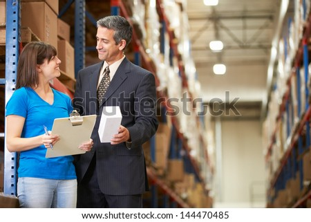 Businessman And Female Worker In Distribution Warehouse