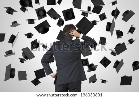 Businessman and flying graduation hats