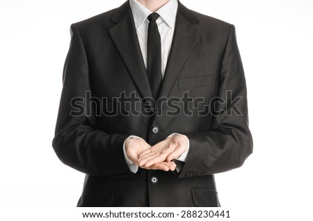 Businessman and gesture topic: a man in a black suit and tie two hands clasped in front of him isolated on a white background in studio