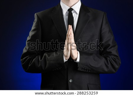 Businessman and gesture topic: a man in a black suit and white shirt holds her hands together in front of you and prays, meditates on a dark blue background in studio isolated - stock photo