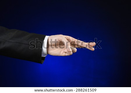 Businessman and gesture topic: a man in a black suit and white shirt showing hand gesture on an isolated dark blue background in studio - stock photo