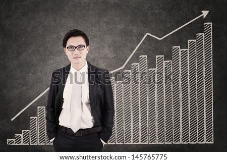Businessman and growing bar chart in class - stock photo