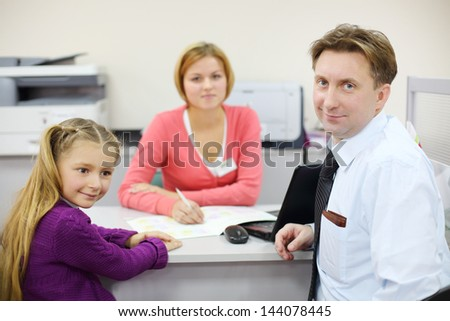 Businessman and her daughter sit in office of realtor. Focus on man and girl. - stock photo