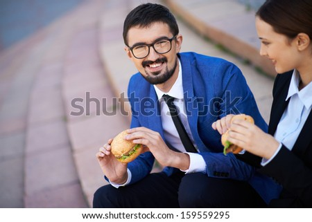 Businessman and his colleague eating sandwiches outside - stock photo
