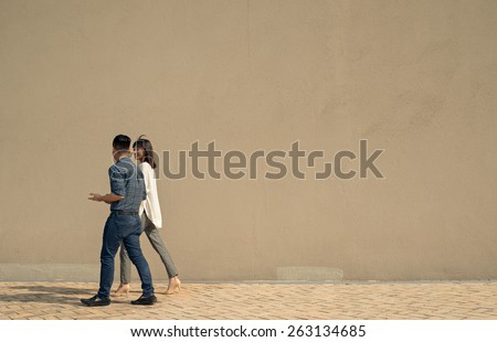 Businessman and his female colleague walking along the wall