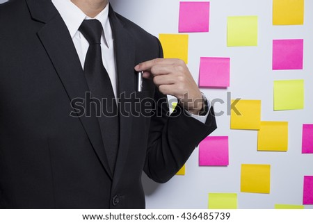 Businessman and his pen on notepaper background