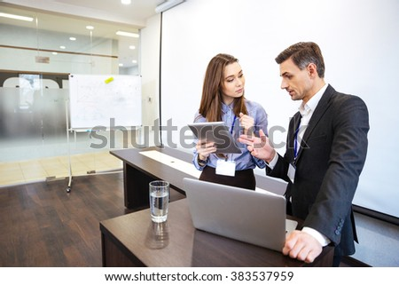 Businessman and his secretary standing and planning work in office - stock photo