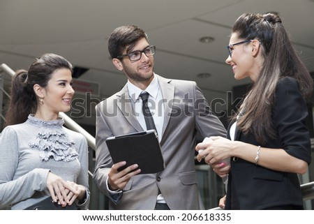 Businessman and his team working on the digital tablet - stock photo