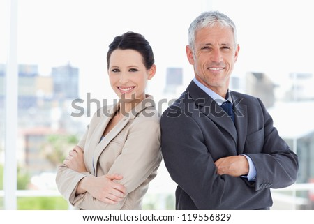 Businessman and his young secretary standing upright side by side - stock photo