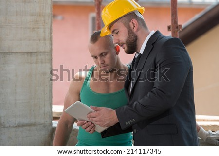Businessman And Industrial Worker Looking At Tablet PC - Group Of Male Architect And Construction Worker On Construction Site - stock photo
