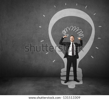 businessman and lamp drawn on the wall - stock photo