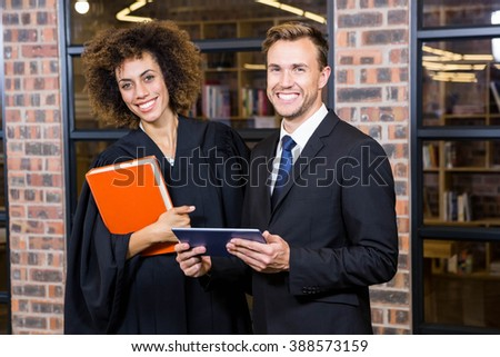 Businessman and lawyer standing near library with digital tablet and law book - stock photo