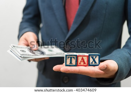 Businessman and money with TAX word on hand  - stock photo