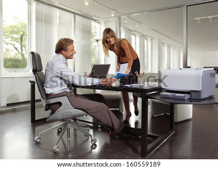 businessman and secretary using copy machine - stock photo
