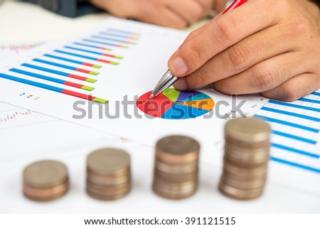 Businessman and Stack Of Coins with investment graph report  - stock photo