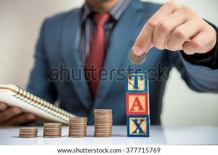 Businessman and Stack Of Coins with TAX word  - stock photo