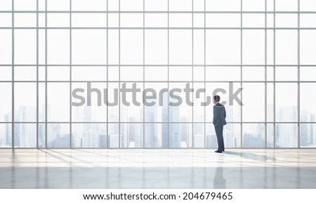 Businessman and sunny office interior - stock photo