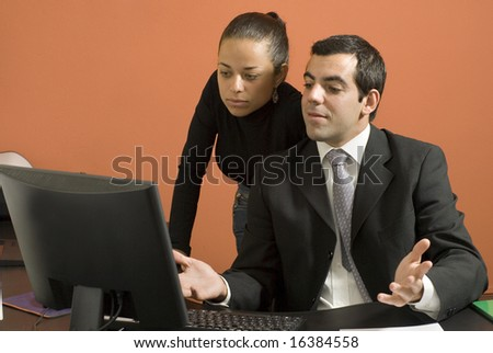 Businessman and woman at desk looking at a computer. He is looking surprised with his hands up. Horizontally framed photo - stock photo