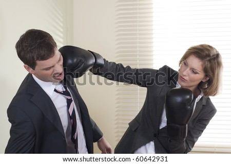 Businessman and woman boxing in the office
