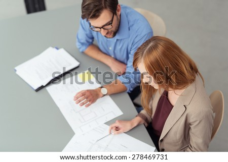 Businessman and woman discussing a document as they sit together at a desk working in the office, high angle view