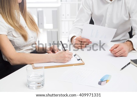 Businessman and woman discussing business report at office desk - stock photo