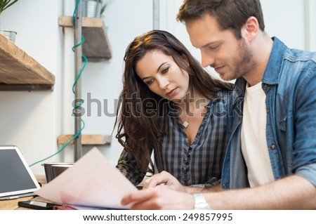 Businessman and woman going through paperwork together in office  - stock photo
