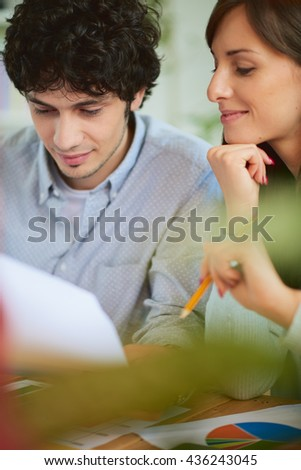 Businessman and woman going through paperwork together in office.