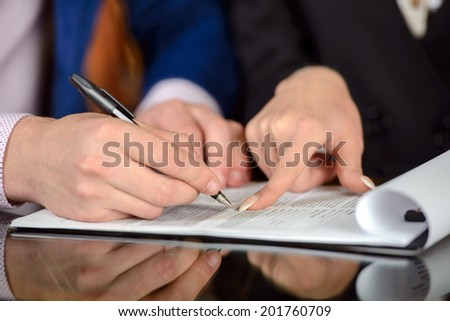 Businessman and woman hand signing contract paper - stock photo