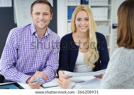 Businessman and woman in a meeting in the office sitting side by side at a table with a colleague smiling at the camera